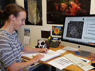 Kepler scientist at work in front of data from telescope.
