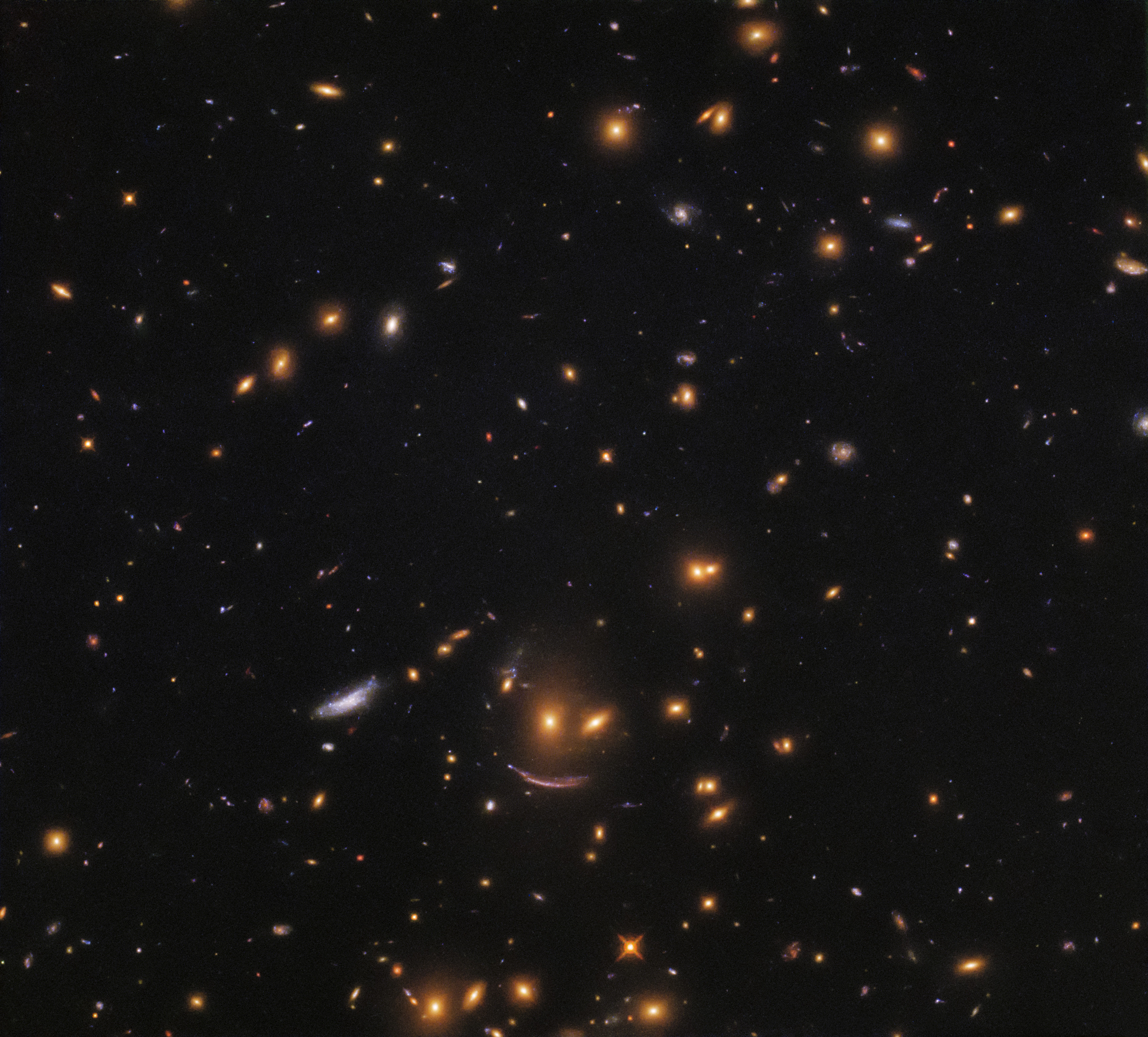 A smiley face is seen in a field of stars amid the black of space.