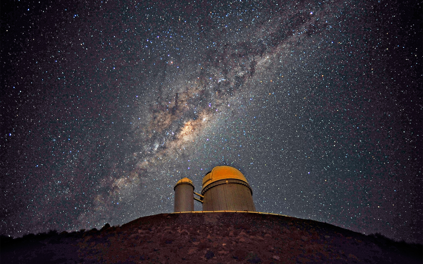 The Milky Way Galaxy is seen across the night skt over a domed telescope.