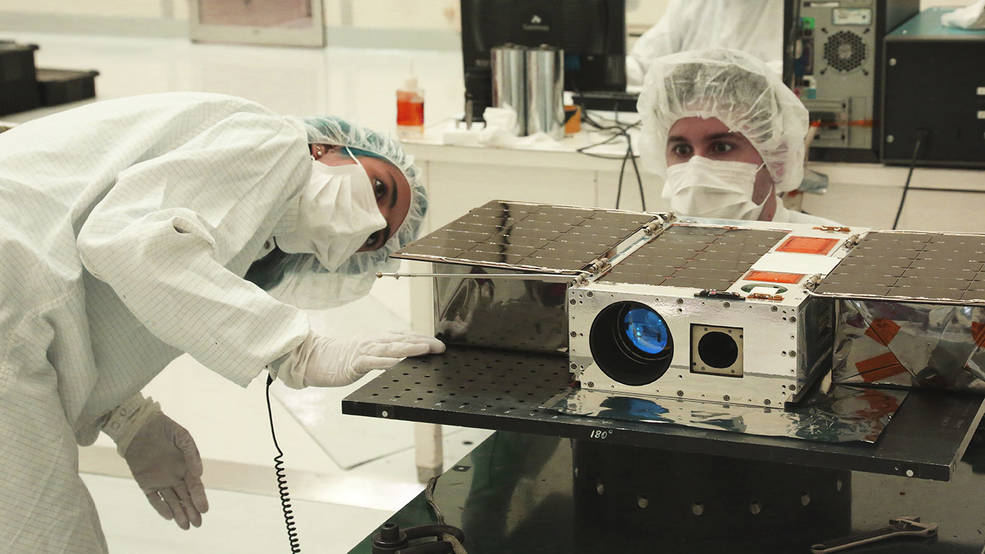 A small satellite called ASTERIA is seen in the clean room with two engineers
