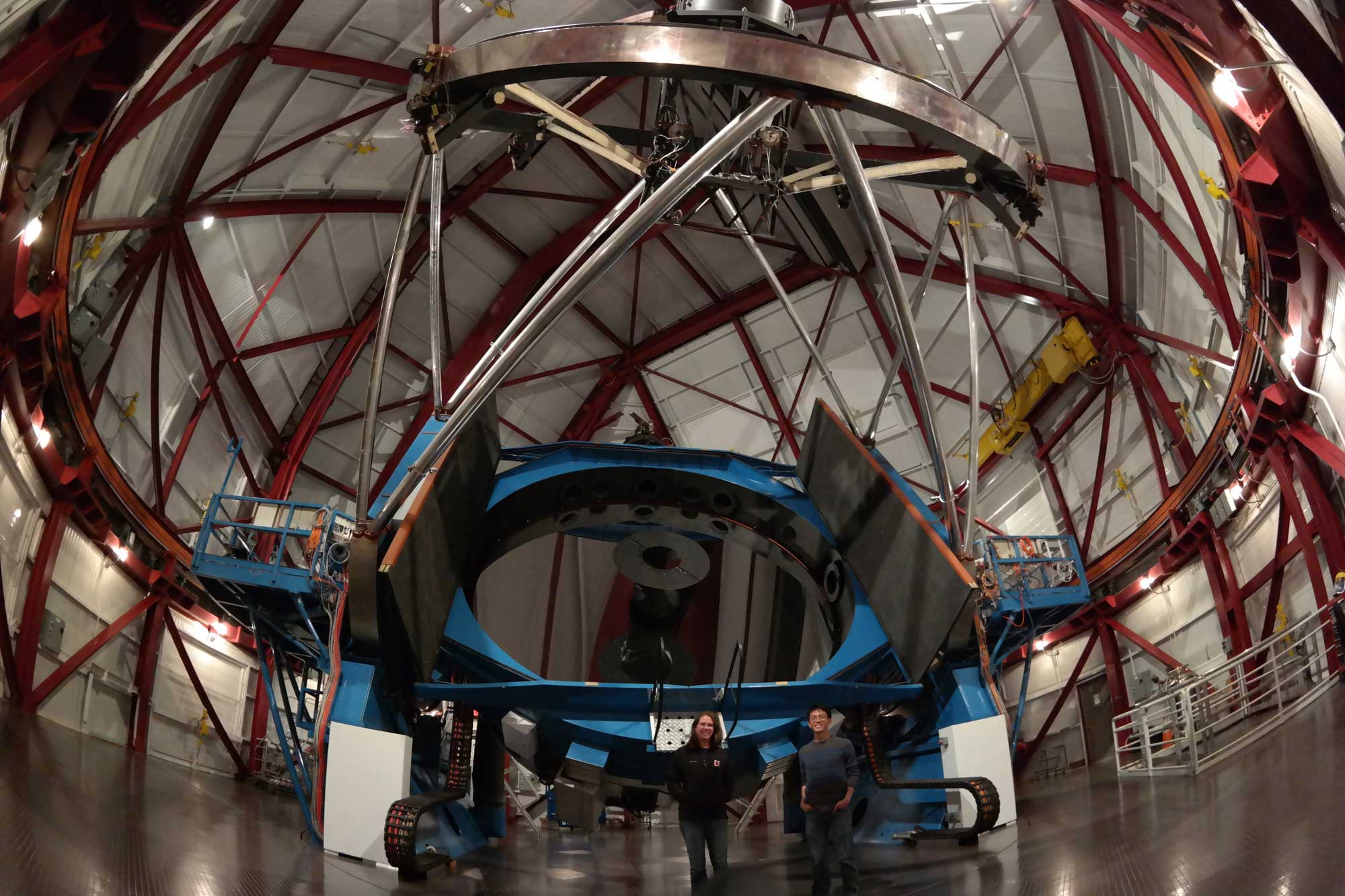 Two astronomers are seen inside the dome of the Magellan II telescope