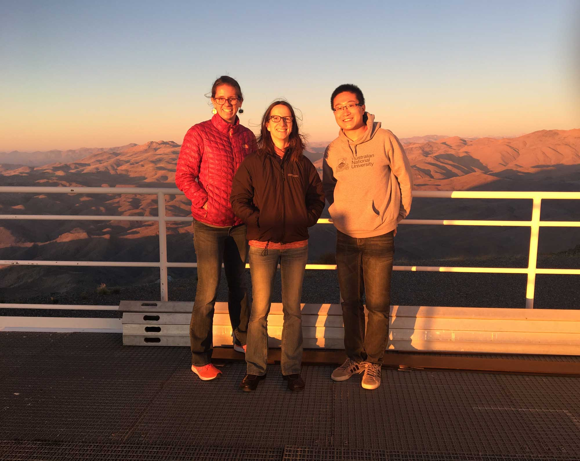 Three people stand on an overlook with mountains beyond.