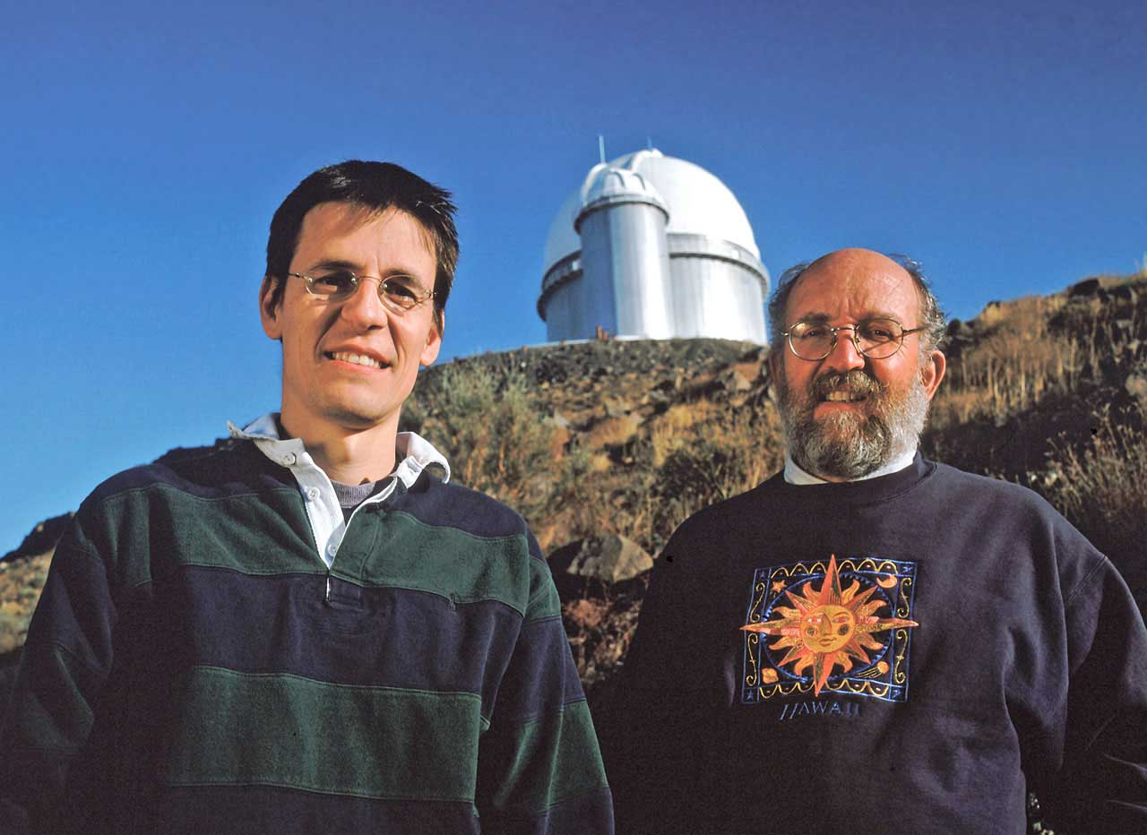 Two astronomers in front of an observatory on a bright day.