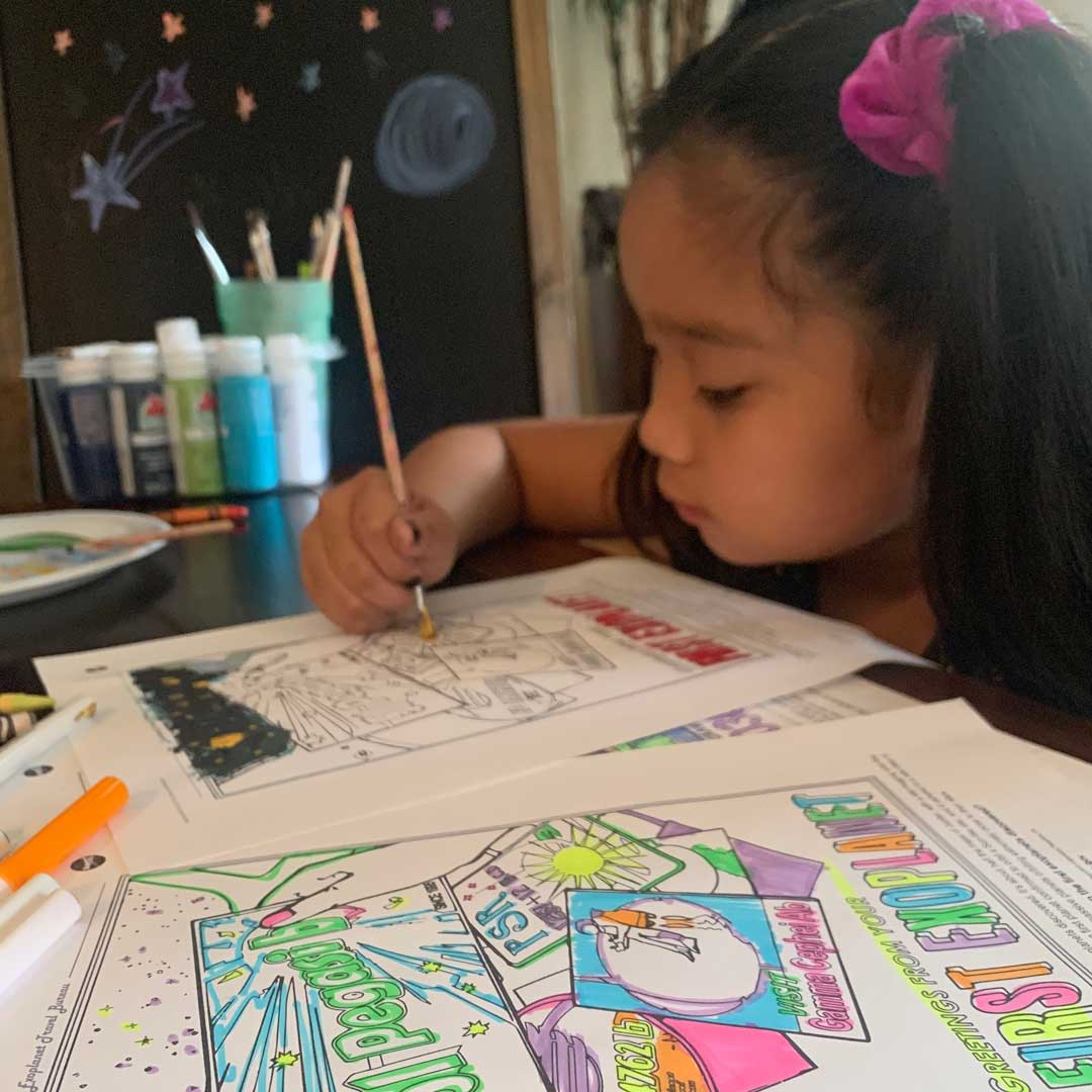 A young girl paints Exoplanet Coloring Book pages.