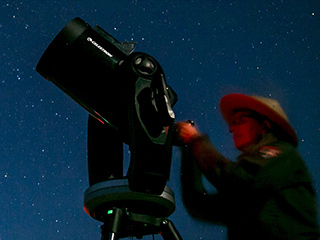 A park ranger at Dinosaur National Monument adjusts a telescope during a night sky program, with a star filled sky behind her.