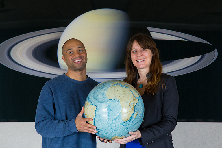 Ramses Ramirez, left, and Lisa Kaltenegger hold a replica of our own habitable world, as they hunt for other places in the universe where life can thrive. Credit: Chris Kitchen/University Photo