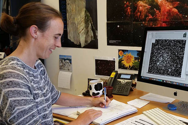 Photo of Ann Marie Cody at her desk with a space image on her monitor.