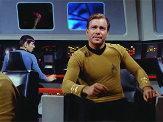 Captain Kirk sits in his chair on the bridge of the U.S.S. Enterprise.