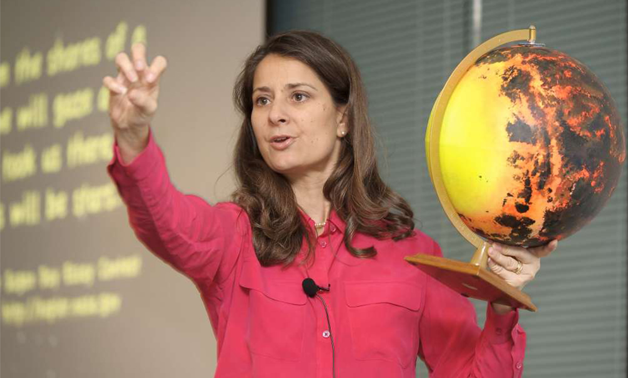 Photo of Natalie Batalha holding a model of an exoplanet she discovered.