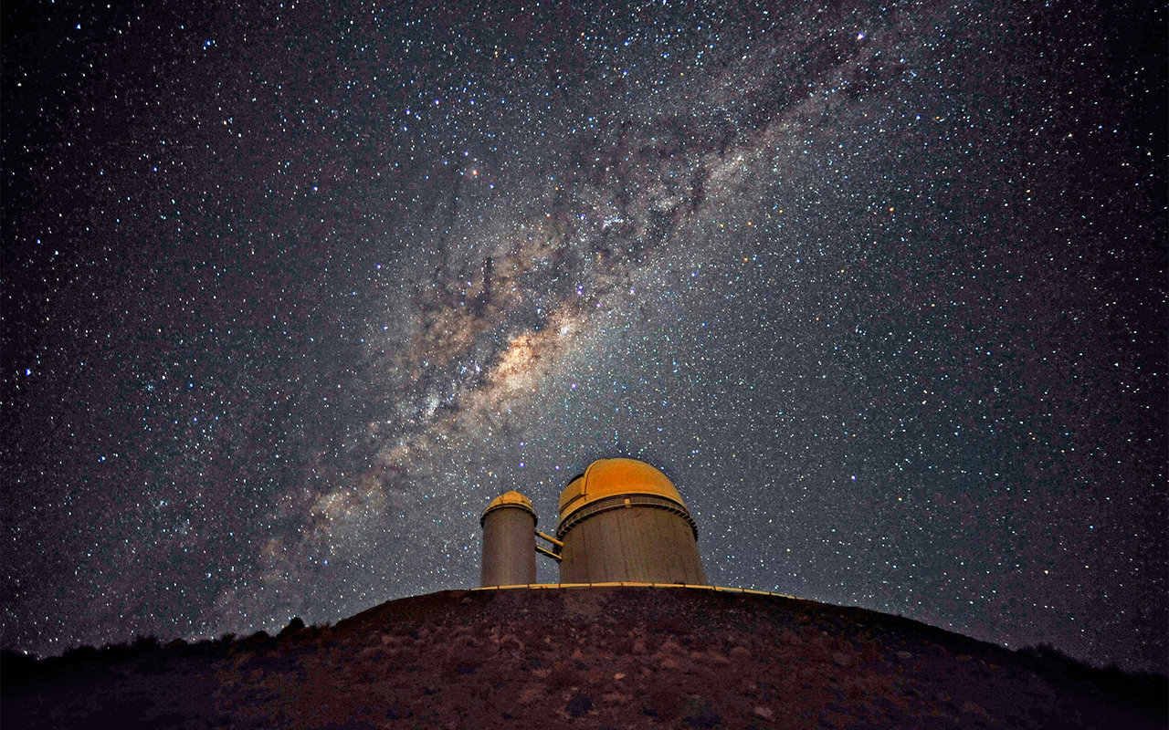 Photo of the La Silla observatory, with the Milky Way center above.