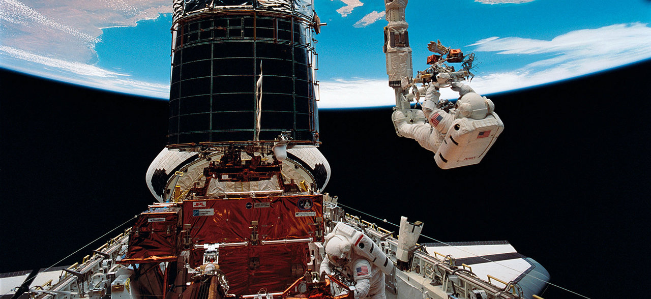An astronaut is seen at the end of a robotic arm to repair the Hubble Space Telescope.