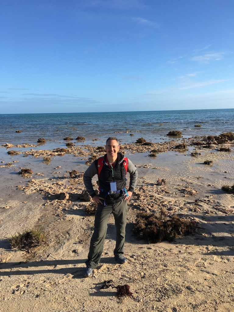 Nick Siegler, the chief technologist for NASA's Exoplanet Exploration Program, at Western Australia's Shark Bay. The dark, rounded forms in the background are stromatolites, one of Earth's most ancient lifeforms.