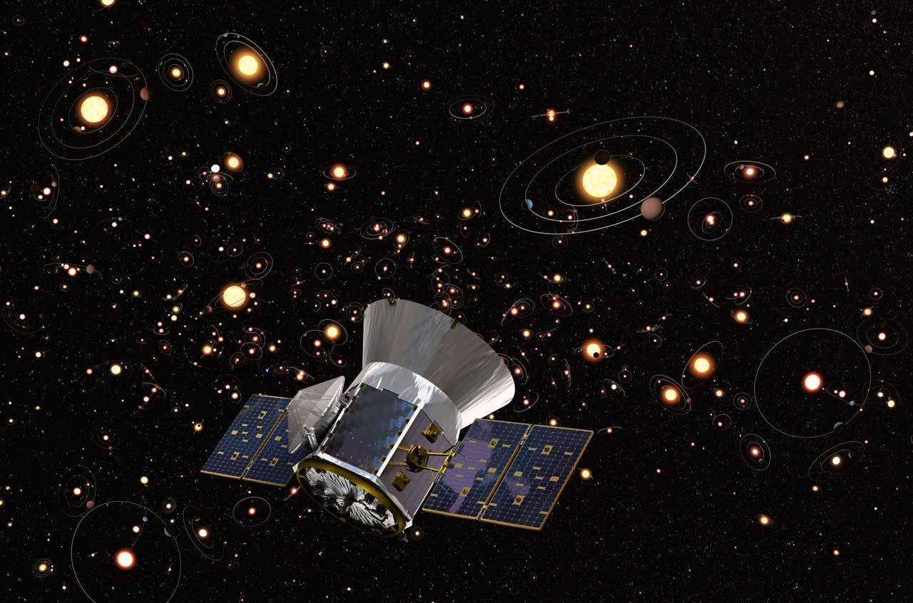 The TESS spacecraft is seen before a background of stars and exoplanets in orbit.