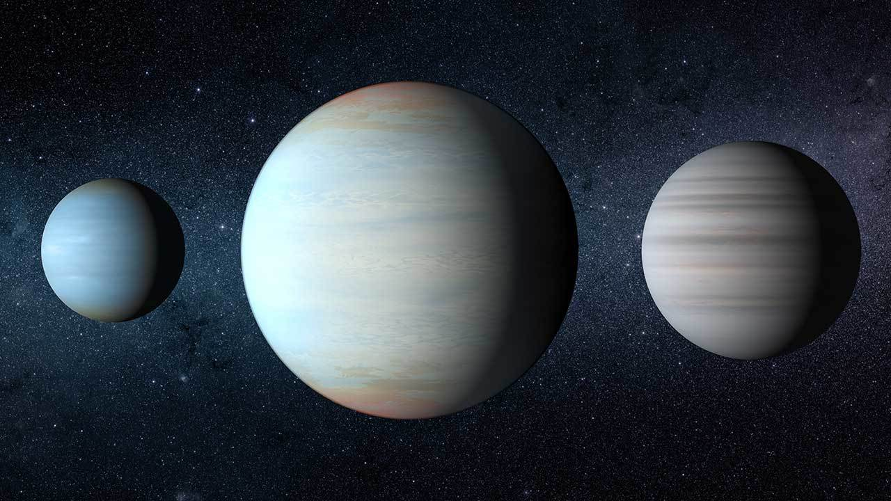 Three exoplanets are shown, with two smaller planets around the third much larger planet.