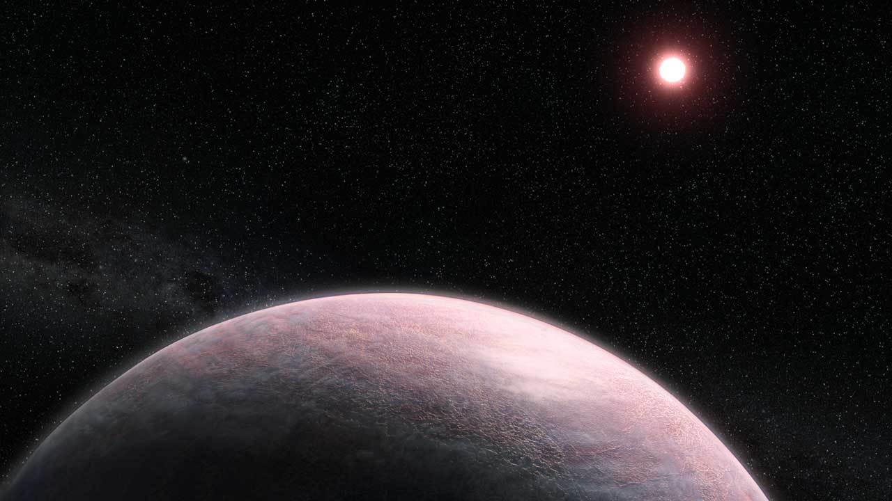 A reddish, terrestrial exoplanet is seen in orbit of its red dwarf star.