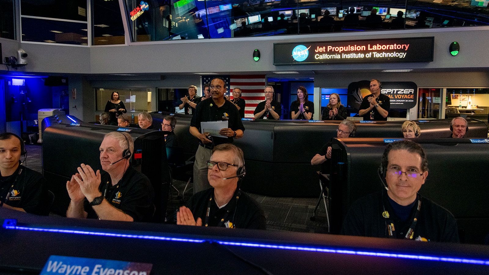 Men and women applauding in mission control as Spitzer's mission is declared over.